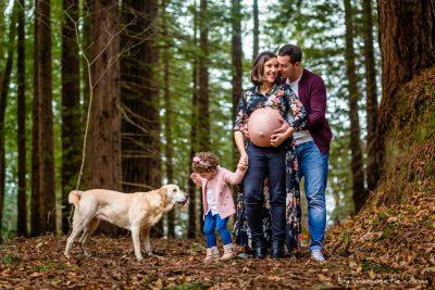 Familia esperando un hijo, de marido, hija mayor y perro en un bosque por un fotógrafo de Castro Urdiales