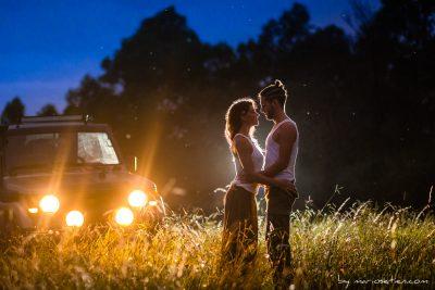 Pareja de novios abrazados en un prado al anochecer iluminados por la luz de un todo terreno en Maliaño Cantabria