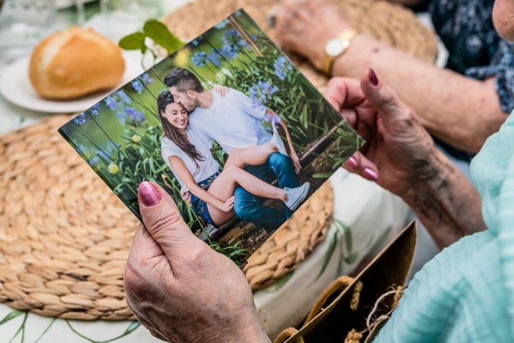 Las manos de una abuela sujetando una foto que le han regalado
