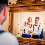 Novio y cuñado pasándolo bien mientras se visten frente al espejo en Cantabria