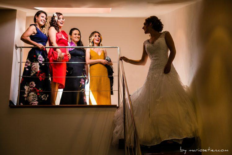 Novia con su vestido bajando por las escaleras ante la mirada de sus amigas