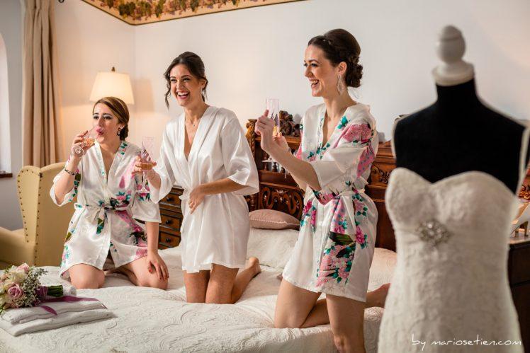 Novia y damas de honor brindando junto al vestido de novia
