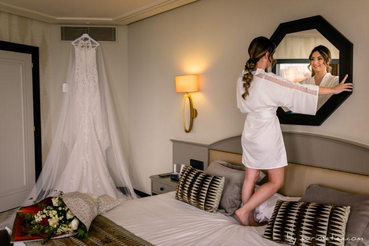 novia mirándose al espejo con su vestido al fondo