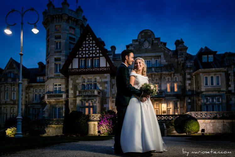 Pareja de novios en el Palacio de la Magdalena de Santander abrazándose frente al palacio, de noche