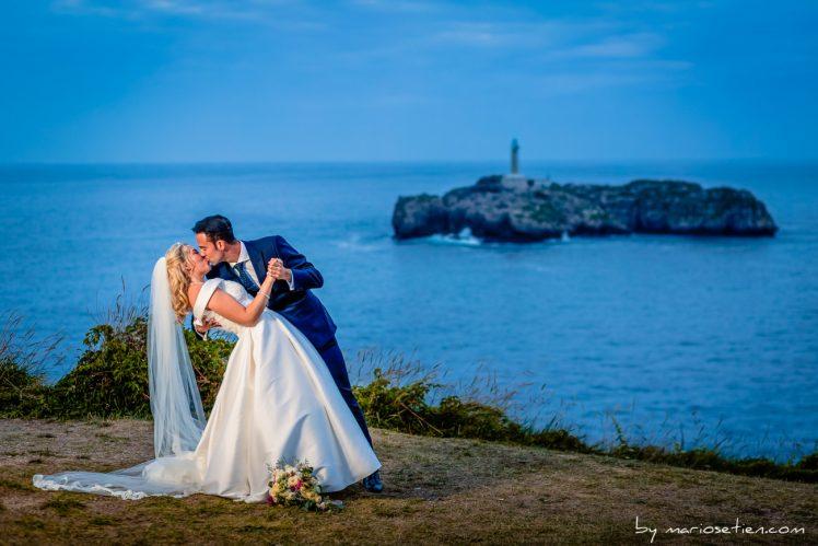 Beso apasionado de dos novios en el Palacio de la Magdalena con el faro de la Isla de Mouro al fondo