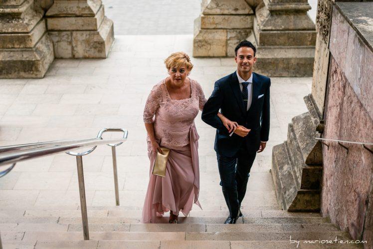 Novio subiendo las escaleras con la madrina del brazo, en el Palacio de la Magdalena de Santander para una boda civil