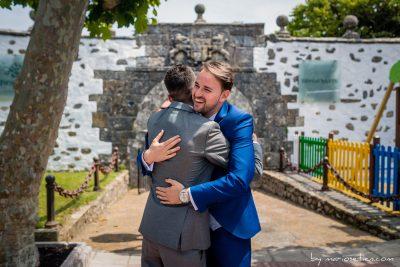 Novio abrazando a un invitado en la portalada de Viares