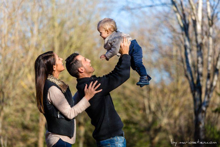 mamá y papá con su bebé en el aire en Santiago de Cartes