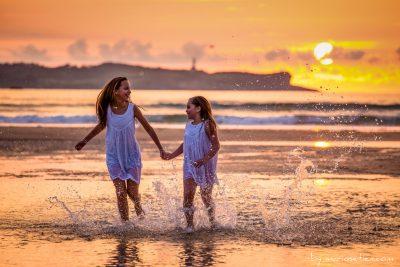Hermanas disfrutando de un atardecer en Loredo corriendo por la playa